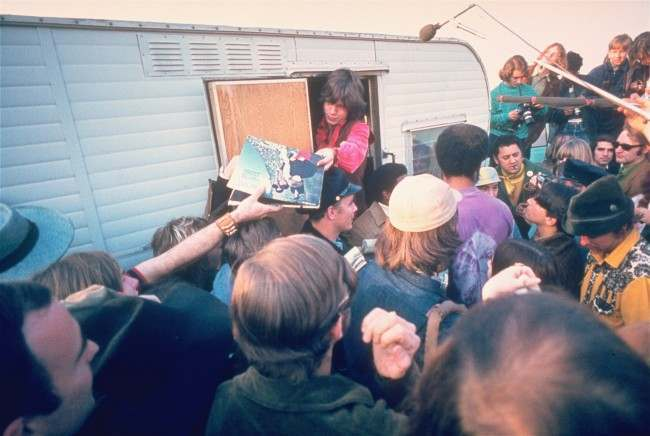 The Rolling Stones lead singer Mick Jagger signs autographs for fans at the Altamont Race Track, Dec. 8, 1969. Later, the Stones gave a concert where one fan was stabbed to death by a Hells Angels member.
