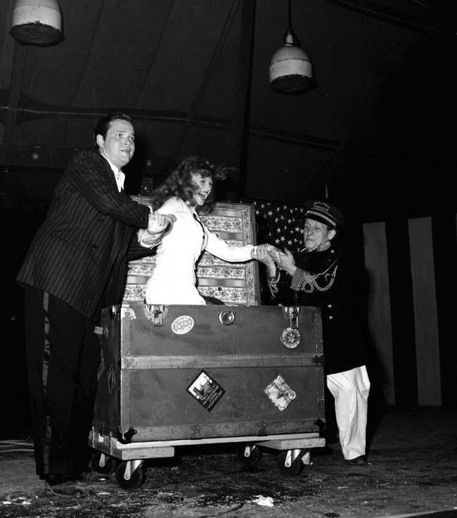 Soldiers cheered when Rita Hayworth, film star, was found again in a trunk, after Orson Welles, director-magician, had tied her in ropes and caused her to vanish on August 9, 1943 in Hollywood. (AP Photo)