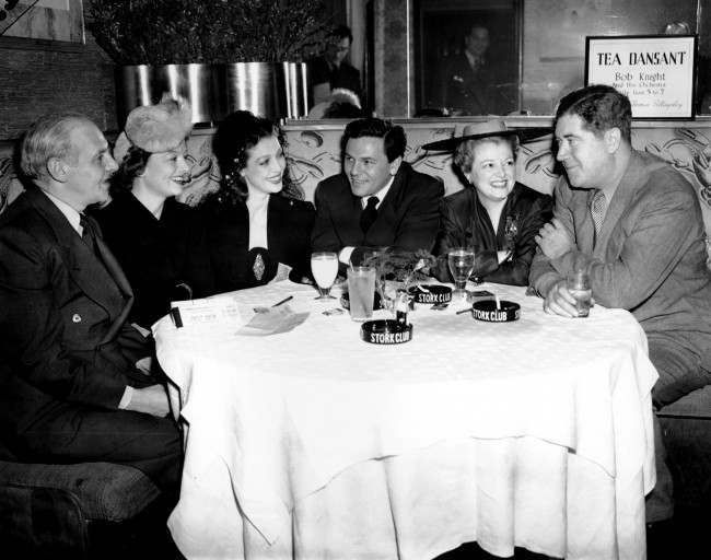 Writers and movie stars gather at New York's Stork Club, March 8, 1942, as they prepare for a World War II Navy Relief Show, two days away, at Madison Square Garden. From left are: columnist Walter Winchell, Myrna Loy, Loretta Young, John Garfield, Janet Gaynor and Quentin Reynolds, author and war correspondent. (AP Photo/Matty Zimmermann)