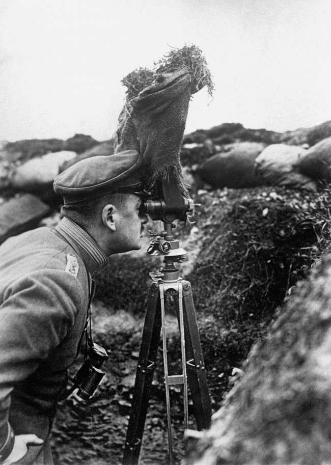 A German Army officer taking observations from a trench by means of a pair of periscope binoculars screened with sacking.