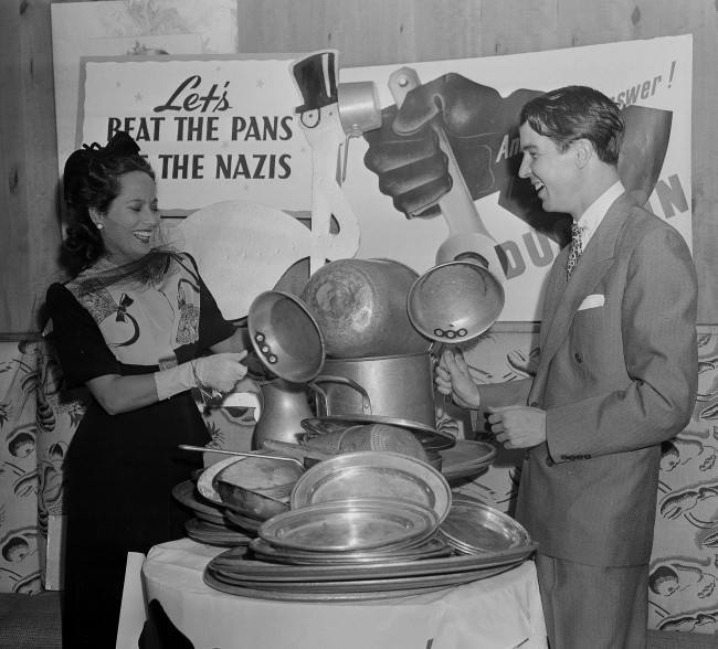 Merle Oberon, movie star, and Alfred G. Vanderbilt raise a din by beating pans at an aluminum-collection breakfast at the stork club in New York, July 23, 1941. The price of admission was a piece of aluminum ware. (AP Photo)