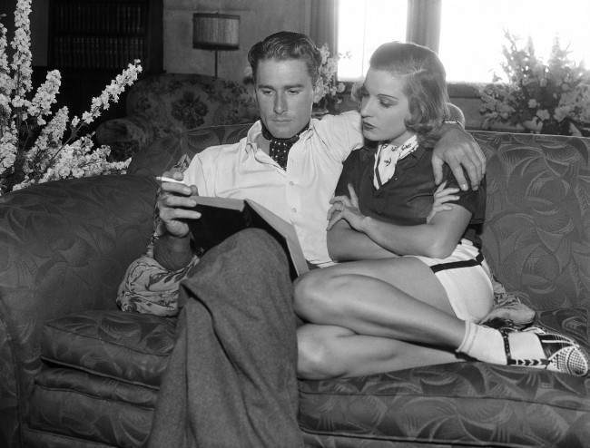 Back home from their matrimonial flight to Yuma, Ariz., Lily Damita, film actress, and Errol Flynn, actor  are the perfect picture of domestic bliss in their Hollywood home, Los Angeles June 25, 1935, as they enjoy the same book together. (AP Photo)