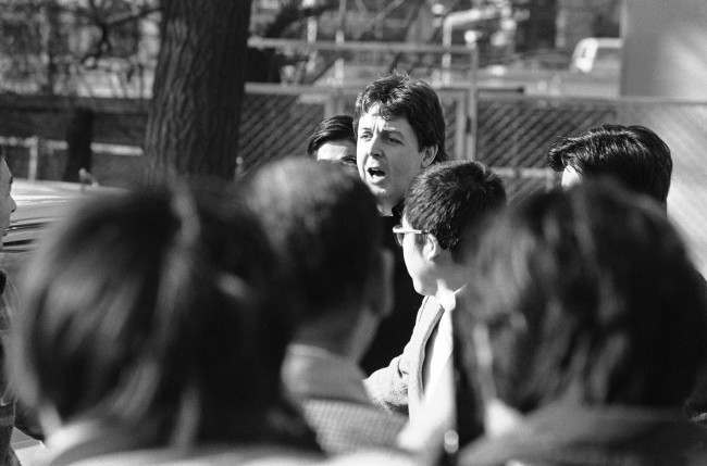Former Beatle Paul McCartney calls a greeting to a handful of teenage fans who waited outside a drug investigation unit for his arrival in Tokyo on Jan. 17, 1980. McCartney, arrested after Customs officers found Marijuana in his luggage, spent the night in jail, was taken to the drug unit for questioning. (AP Photo/Sadayuki Mikami)