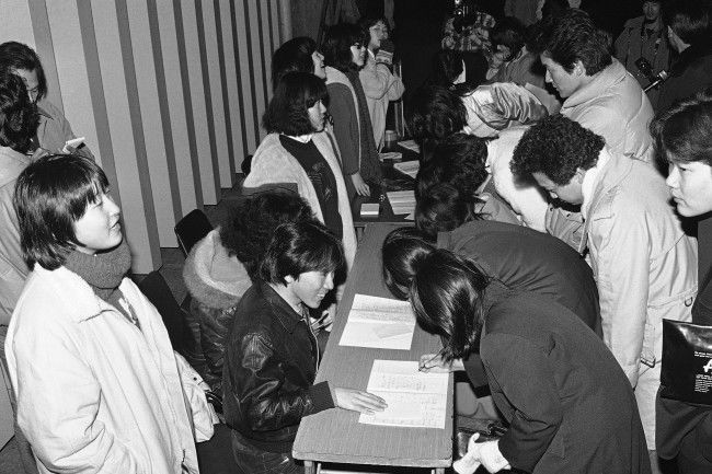 "Members of Tokyo Fan Club of ""Wings,"" left, collect signatures from young rock enthusiasts outside the Budokan Hall, where the British rock group was to give its first concert in Tokyo on Monday, Jan. 21, 1980. The concert was canceled because its leader Paul McCartney was arrested last week for Marijuana possession. The fans, who came to the hall for a refund, were willing to sign their names at the request of the fan club, which said it intended to give the signed note book to McCartney to comfort him. (AP Photo/Sadayuki Mikami)"
