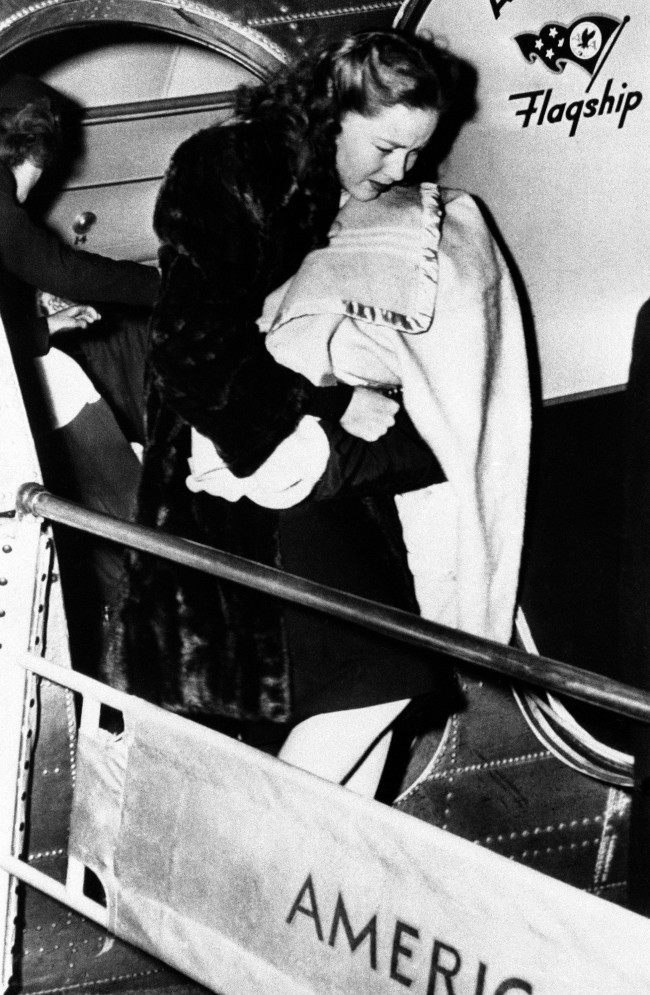 Nora Eddington Flynn, 18 year old cigar store girl, carries her infant child, Deidre Eddington Flynn from the plane on arrival at Burbank, California, on April 3, 1945. Movie film star, Errol Flynn acknowledged marrying the girl secretly. AP/Press Association Images