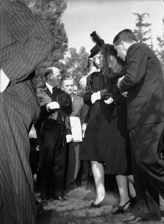 The grieving widow, Mabel Ward Mix, center, and daughter, Thomasina Mix Matthews, of Tom Mix, beloved cowboy actor of the movies and circus who was killed in an automobile accident in Arizona, are shown as they arrived for funeral services at Forest Lawn in Glendale, California on Oct. 16, 1940. With them is Thomasina's' husband, Bernard Matthews. (AP Photo/Harold Filan)