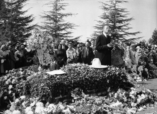 More than 2000 persons gathered at Forest Lawn in Glendale, California Oct. 16, 1940, as Tom Mix, famous cowboy movie actor killed in a desert highway accident in Arizona, was buried following funeral services in the Little Church of the Flowers. The Rev. J. Whitcomb Brougher, officiates here beside the casket, on which rests Mix''s ten-gall on hat (AP Photo/Harold Filan)