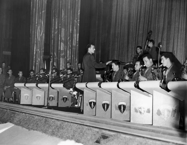 "Capt. Glenn Miller, who has come to Britain with the American band of the Supreme Allied Command, gave Londoners a treat by appearing with his band at a gala premiere of the new Bing Crosby Film, ""Going My Way,"" at a West End Movie Theater in London, August 5, 1944. Proceeds from the premiere were used to aid London's Stage Door Canteen, soon to be opened. The band leader is leading is army band in a thirty-minute session of swing music during the stage door canteen benefit. (AP Photo)"