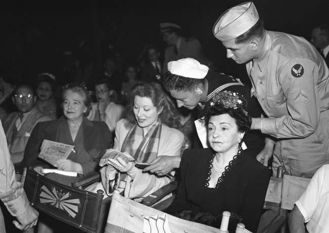 Service men keep Greer Garson, film star, pushing the autograph pencil at Orson Welles' big music show in Hollywood, Los Angeles, free to men in uniform, on August 9, 1943. (AP Photo)