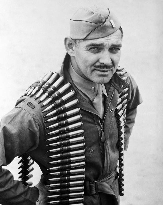 First Lieut. Clark Gable, former movie actor now an aerial gunner in the Army Air Forces, wears a double shoulder sling of .50 caliber machine gun bullets in taking off on a practice firing mission at Tyndall Field in Panama City, Florida on Jan. 20, 1943. (AP Photo)