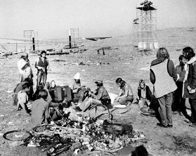 Some rock music fans still play, cook and relax in the aftermath of yesterday's free concert at the Altamont Speedway near Livermore, Dec. 7, 1969. In the background the frameworks of the stage and light stands are visible. The free concert, already dubbed Woodstock West, attracted more than 300,000 people. (AP Photo)