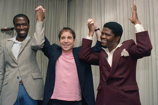 "Singer-songwriter Paul Simon is joined by Albert Mazibuko, left, and Joseph Shabalala, right, at a news conference in New York, Aug. 25, 1986, to introduce Simon's new album, ""Graceland."" Mazibuko and Shabalala are two of the many South Africa musicians and singers who collaborated with Simon on his new album which blends the sounds of American pop music with that of black South Africa. (AP Photo/Marty Lederhandler)"