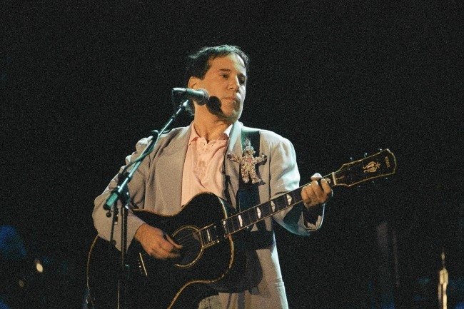 U.S. singer Paul Simon performs during his concert in Johannesburg, Jan. 11, 1992. Simon is the first international star to perform in South Africa since the lifting of the cultural boycott last year. A small group of black militants staged a demonstration outside the stadium. (AP Photo/Adil Bradlow)