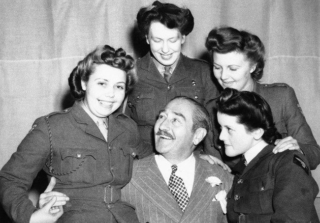 Adolphe Menjou, the famous film star, is seen making friends with three A.T.S. girls and A.W.A.A. girls at his first troop concert in this country June 14, 1943. (AP Photo)