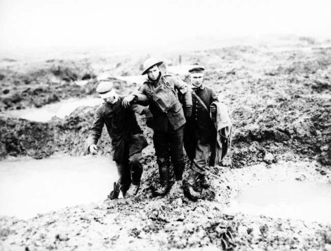 Canadian and German wounded help one another through the mud during the capture of Passchendaele in Belgium sometime between July and November 1917. (AP Photo)