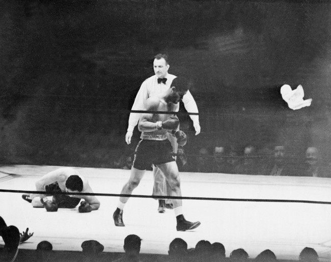 Heavyweight boxer Joe Louis walks away to a neutral corner as challenger Max Schmeling lies on the canvas in the first and final round of their 15-round rematch at Yankee Stadium in New York City, June 22, 1938. Schmeling's corner surrenders by throwing in a white towel into the ring at right. Referee Arthur Donovan called the match after 2 minutes and four seconds of action. (AP Photo)