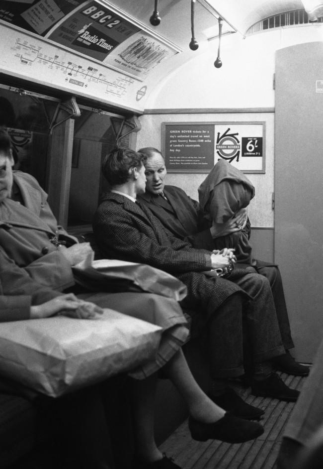 Unnoticed by most of the other passengers on the Central Line underground train, West Ham United manger Ron Greenwood holds the Football Association Cup, wrapped in a red cloth, as he takes a corner seat at Tottenham Court Road Station, in London, on May 4, 1964. Greenwood was taking the Cup back to West Ham after he and his team had watched a special West End showing of a Cinemascope colour film of highlights of Cup Final at Wembley on Saturday. West Ham beat Preston North End 3-2.