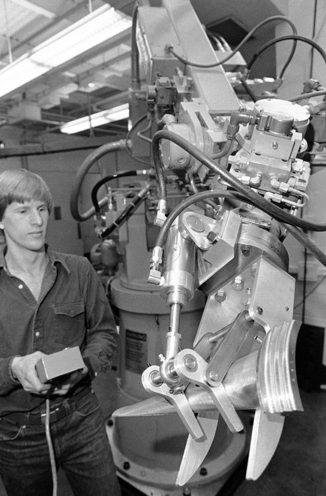 "Mark Cutkowsky, a research assistant in the newly-formed Robotics Institute at Carnegie-Mellon University, controls a computer which operates a robot involved in machining turbine blades from raw metal in Pittsburgh, Nov. 29, 1980. The robot is part of a major research project underway that hopes to come up with robot systems that can be applied to a ""factory of the future""."