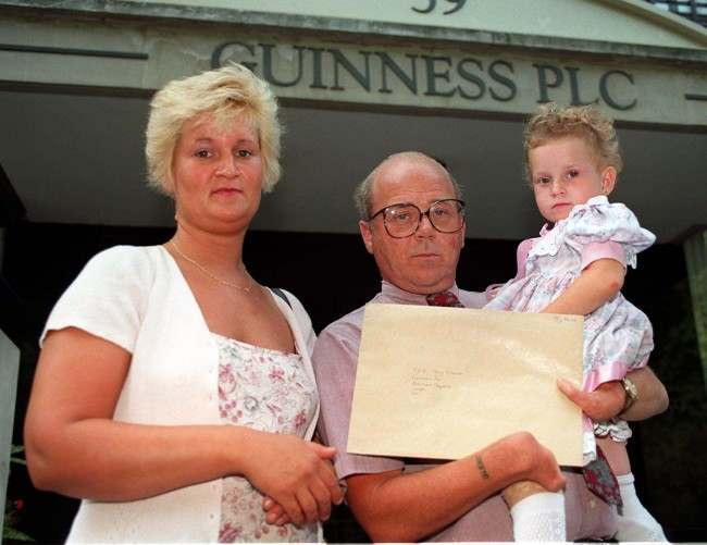 Four-year-old Georgina Harrison with her mother, Deborah and father, Glenn outside the London office of Guinness plc today (Tuesday) where they presented the company with new evidence which suggests that the effects of the thalidomide drug could be hereditary. Georgina, daughter of Mr Harrison, a thalidomide victim himself, was born with deformities akin to those prevalent in thalidomide cases.