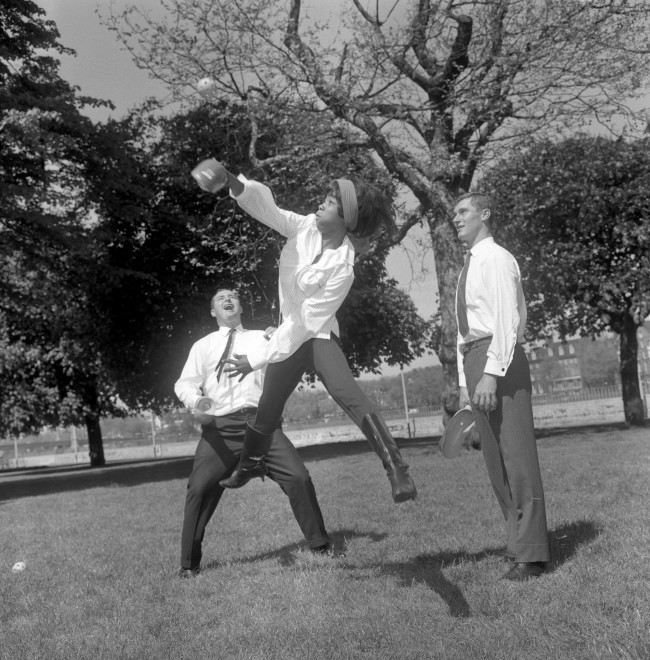 Sixteen year-old Pop singer Millie tries out Slingball, a new ball game having its first UK public demonstration at Battersea Pleasure Gardens. With her are Australia cricketers Barry Jarman [right] and Bob Cowper.