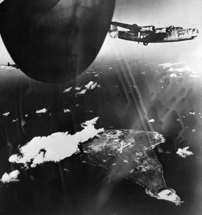 While U.S. B-24 (Liberators) soar high above the Japanese airbase on Iwo Jima in the Volcano Islands, Japan, bombs dropped from the planes explode on the island on Dec. 21, 1944. Volcano at lower tip of island.