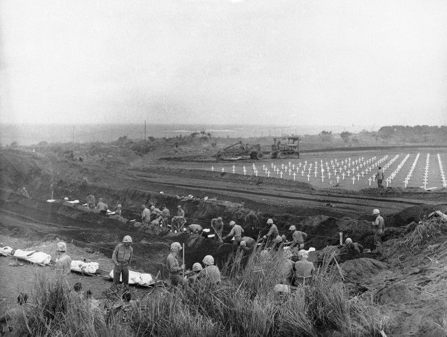 U.S. Marines dig graves in the Fifth Marine Division cemetery on Iwo Jima, Japan, for the shrouded bodies of their buddies on March 30, 1945.
