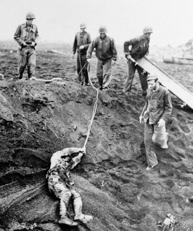 The first Japanese prisoner to be taken on Iwo Jima, Japan, is dragged from shell hole on May 16, 1945, where he lay buried for 1œ days, playing dead to Marines who used it for a fox hole. After knocking away a live grenade that lay a few inches from his hand, Marines dragged him out after he promised an interpreter that he would offer no resistance. A stretcher was thrown down and he rolled on it and was then lifted out.