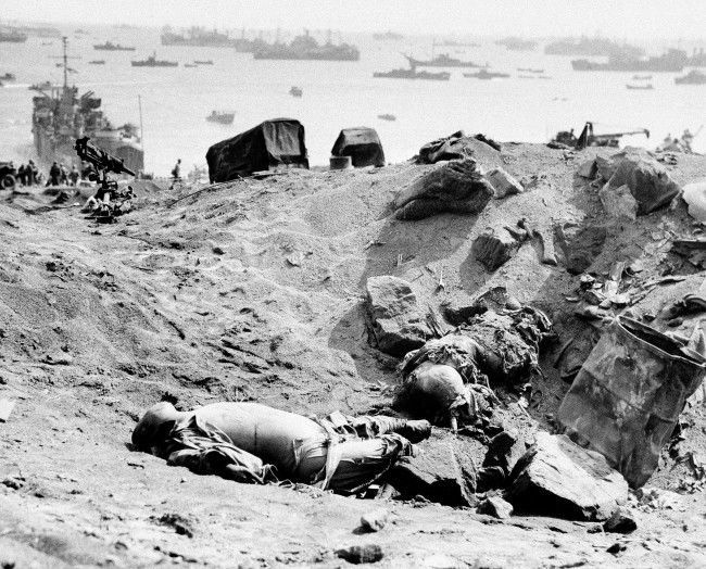 Two Japanese soldiers lay dead from the invasion armada seen in the background in Japan on March 1, 1945. A Coast Guard LST pushes its blunt nose on the beach at left, discharging heavy mechanized equipment.