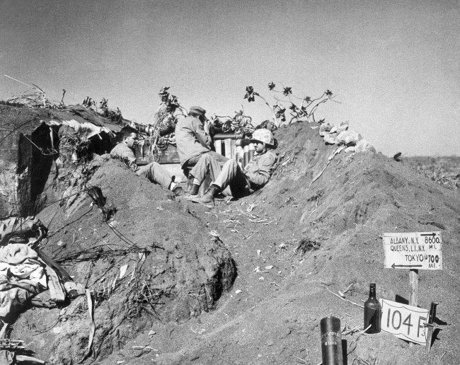 U.S. Marines with a coast guard combat photographer found crouching in a listening post dug in Iwo Jima''s coffee grounds sands, Japan on March 16, 1945.