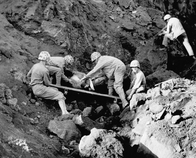 Marine stretcher bearers place a Japanese prisoner on a litter to be carried to the rear, while another Marine covers a cave entrance with his automatic rifle at northern Iwo Jima, Japan on March 17, 1945. According to the Marine Corps, this prisoner gave up when he couldn't hold out any longer after ten days without food or water.