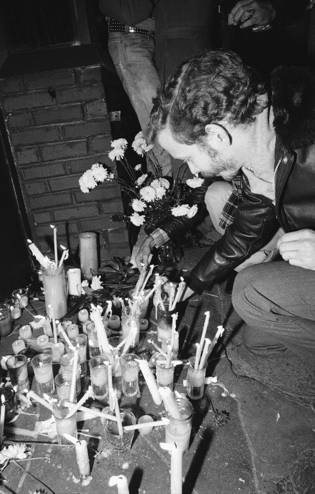 A man places a memorial candle on the sidewalk in front of the Ramrod Bar in New York, Nov. 20, 1980 on the spot where two people were killed and seven others injured in a shooting incident on Wednesday. A former New York transit police officer was arrested and charged with the murders.