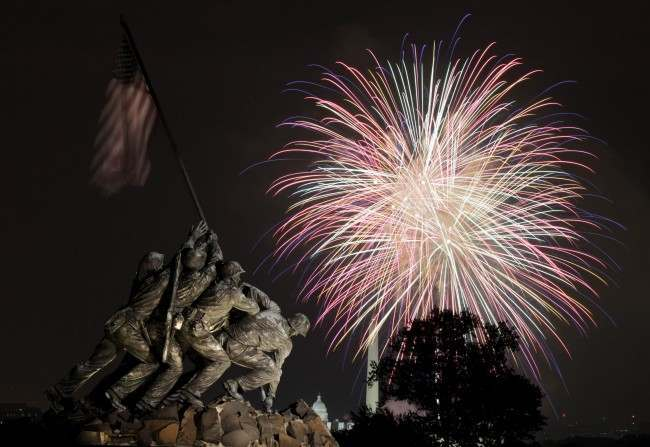 The United States Marine Corps War Memorial, better known as the Iwo Jima Memorial, is seen in Arlington, Va., Monday July 4, 2011, as fireworks burst over Washington, during the annual Fourth of July display. The Washington Monument and the Capitol can be seen in the distance.