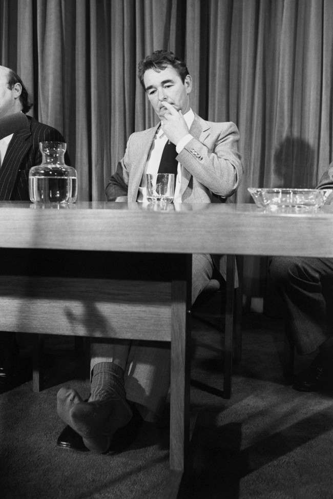 Nottingham Forest Manager Brian Clough, who has taken of his shoes and is showing a hole in his socks, listens during a lunch held by the All Party Football Committee of the House of Commons to talk about problems of violence on the terraces. Brian Clough is considering a future career as a Labour Party member. Date: 12/11/1980