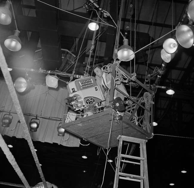 A technician adjusts the television camera that is suspended directly over one of the corners of the ring in which Sonny Liston, heavyweight champion, and challenger Mohammad Ali (Cassius Clay) will battle for the title on Feb. 25, 1964 in Miami Beach, Florida. The fight in Miami beach convention hall will be televised to European stations by satellite and to United States theaters by closed-circuit television.