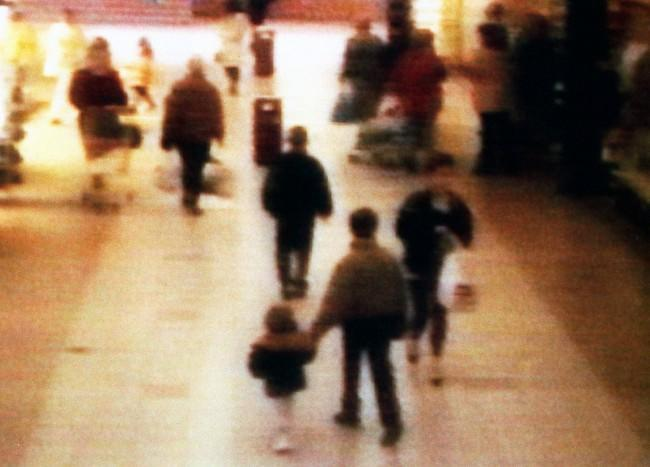 A video still of missing boy James Bulger, aged 2 years old, being led away by a youth in the 'New Strand' shopping centre in the Bootle area of Liverpool. * 12/2/03: Thousands of Merseysiders are expected to observe a one-minute silence to mark the tenth anniversary of James' murder, and the flag over the Town Hall in Liverpool will fly at half-mast in memory of the two-year-old Kirkby boy whose battered body was found on an isolated railway line. His schoolboy killers, Robert Thompson and John Venables, now free and living with new identities, were detained indefinitely following a high-profile trial at Preston Crown Court.  Date: 13/02/1993