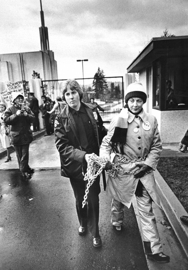Sonia Johnson is led away from the gate of a new $12 million Morman temple by a police officer after she had chained herself to the gate during a pro-Equal Rights Amendment demonstration in Bellevue, Washington on Nov. 17, 1980. Johnson was excommunicated from the Church of Jesus Christ of Latter-Day Saints about a year ago after publicly speaking in favor of the ERA.