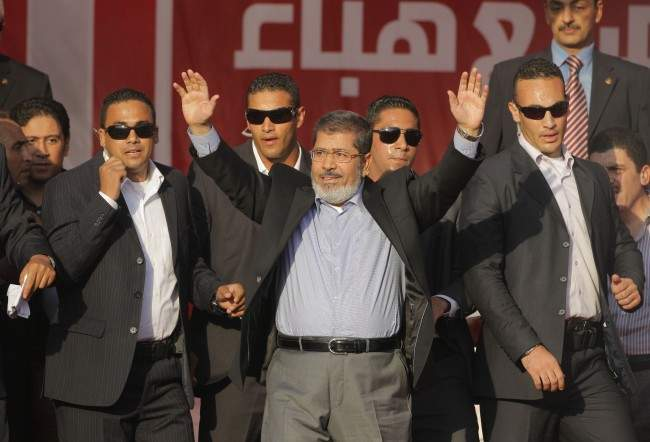 Egypt's President-elect Mohammed Morsi waves to his supporters at Tahrir Square, the focal point of Egyptian uprising, in Cairo, Egypt, Friday, June 29, 2012. In his first public speech addressing tens of thousands of mostly Islamist supporters, Morsi promised Saturday to work to free Omar Abdel-Rahman, the spiritual leader of men convicted in the 1993 World Trade Center bombing.