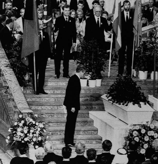 The new Swedish Premier Ingvar Carlsson bows to the coffin with the remains of assassinated late Premier Olof Palme during the funeral service on March 15, 1986 at Stockholm City Hall. Premier Carlsson had addressed the audience before this moment. At center, back to camera, Willy Brandt. Seated.