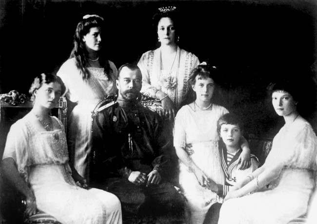 1914: Tsar Nicholas II with his wife Tsarina Alexandra Feodorovna (background), the Tsarevitch (2nd from right) and his four daughters, the Grand Duchesses.
