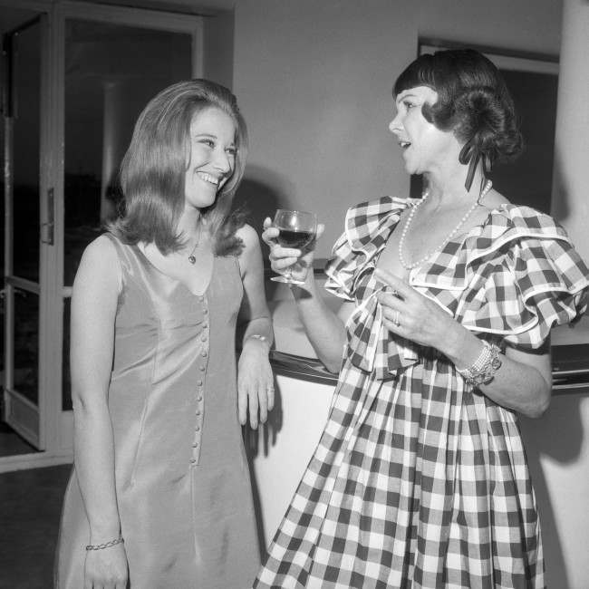 Happy smiles as Ruby Hitchcock, who won the recent 'Miss London Stores' title, learns all about the glamour of Lawn Tennis from America's 'Gorgeous' Gussie Moran, right, at Simpson's department store in Piccadilly, London. They were attending the store's 13th annual Pre-Wimbledon reception. Officials of leading Lawn Tennis associations and other sporting personalities were at the get-together to discuss the forthcoming Wimbledon Championships. Date: 19/06/1968
