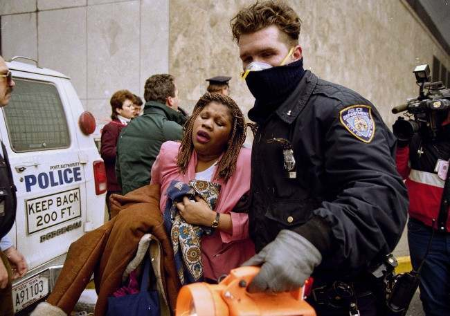 In this file photo of Feb. 26, 1993, a New York City police officer leads a woman to safety following a bomb blast at the World Trade Center. Twenty years ago a group of terrorists blew up explosives in an underground parking garage under one of the towers, killing six people and ushering in an era of terrorism on American soil.