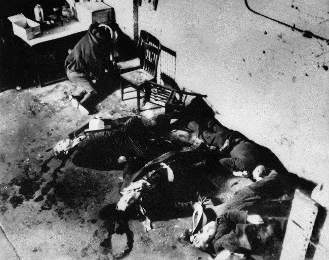 The bodies of six of the men who were slain in a gang-shooting in Chicago's North Side, Feb. 14, 1929. Several of the bodies are huddle together on the floor while another is slumped on chair at the extreme left. The seventh body was taken to the Alexian Brothers Hospital. (AP Photo)