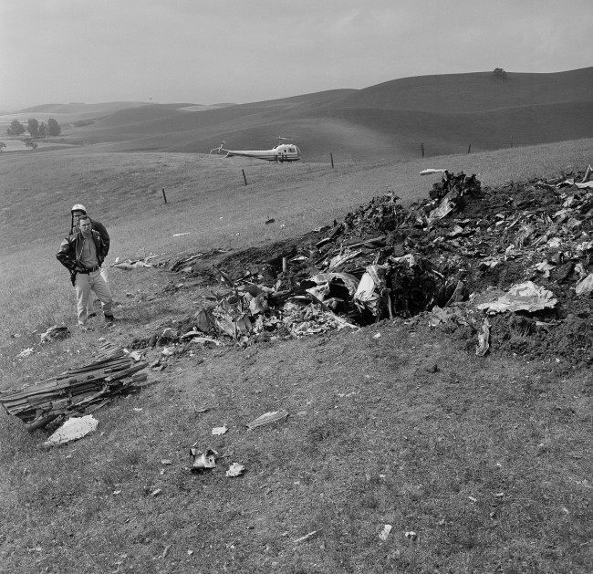 A Contra Costa County sheriff's deputy looks at scattered wreckage of Pacific Air Lines F-27 turboprop that crashed yesterday killing 44 persons, May 7, 1964. The twin-engine transport disintegrated on impact when it dove into the rolling hill area 40 miles east of San Francisco. The plane was on a flight from Reno, Nevada to San Francisco, California.