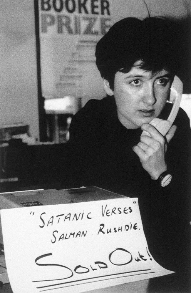 "An unidentified shop asistant places a ""sold out"" notice of Salman Rushdie's ""Satanic Verses"" in a London bookshop, Feb. 16, 1989, while on the telephone to the publishers after having sold out all their copies."