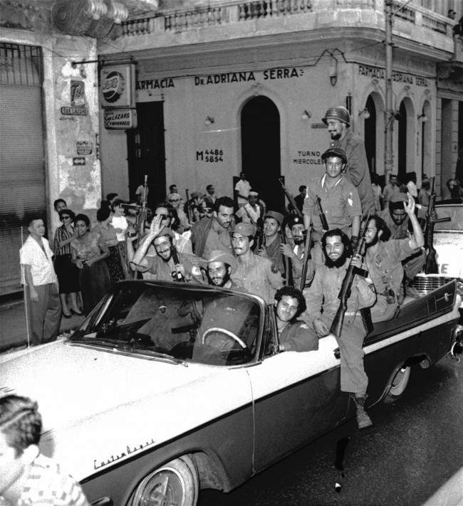 Troops of rebel leader Fidel Castro who have been fighting in the mountains and wilds for the past many months wear broad smiles as they parade through downtown Havana late January 3, 1959, in a show of strength. Thousands jammed the walks to see the parade.