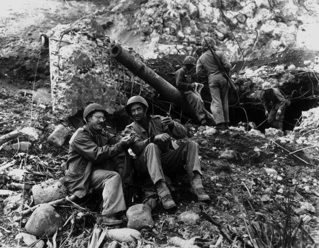Joe Rosenthal, left, AP photographer with the wartime pool, takes time out to rest, March 2, 1945, with Bob Campbell, a Marine from San Francisco, in front of a large Japanese gun knocked out by Marines at the base of Mt. Suribachi. Rosenthal scaled the mountain to make the picture of the U.S. flag being raised there.