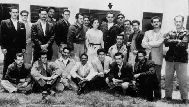 "Twenty-two Cuban exiles arrested for plotting the assassination of President Fulgencio Batista are shown in front of a government office in Mexico City. June 26th, 1956. Fidel Castro, prominent revolutionary, is standing and indicated (arrow), and seated second from left is Ernesto ""Che"" Guevara."