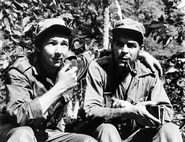 "Raul Castro, left, younger brother of Cuban rebel leader Fidel, has his arm around second-in-command, Ernesto ""Che"" Guevara, Argentine national, in their Sierra de Cristal Mountain stronghold south of Havana, Cuba, during the Cuban revolution in this file photo. June, 1958."