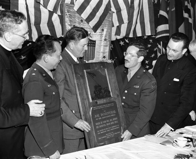 Joe Rosenthal, second from right, Associated Press photographer who took the famed Iwo Jima flag raising picture, is awarded a plaque at a Communion breakfast in New York, April 8, 1945. Looking on from left: Auxiliary bishop James Francis McIntyre of New York; Brig. Gen. Carlos P. Romulo, commissioner of the Philippines; Edward A. Mahar of the Catholic Institute of the Press; Rosenthal; Moderator Rev. Aloysius F. Coogan.