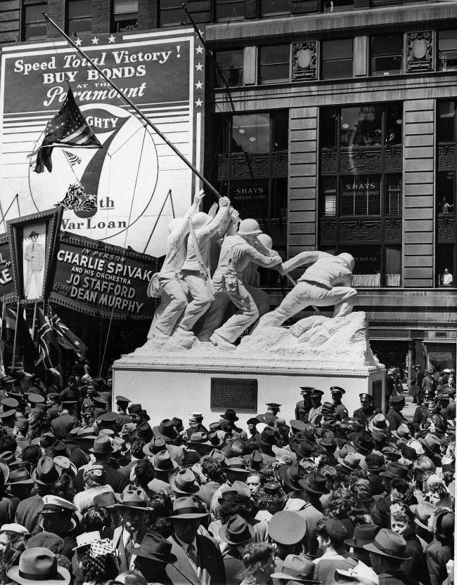 Hundreds look on during the unveiling of the 50-foot statue of the Iwo Jima flag-raising, a reproduction of AP photographer Joe Rosenthal's Pulitzer Prize winning picture, May 11, 1945. The unveiling, at Times Square in New York, officially opened the 7th War Loan Drive. The original flag raised on Iwo Jima is used on the statue.
